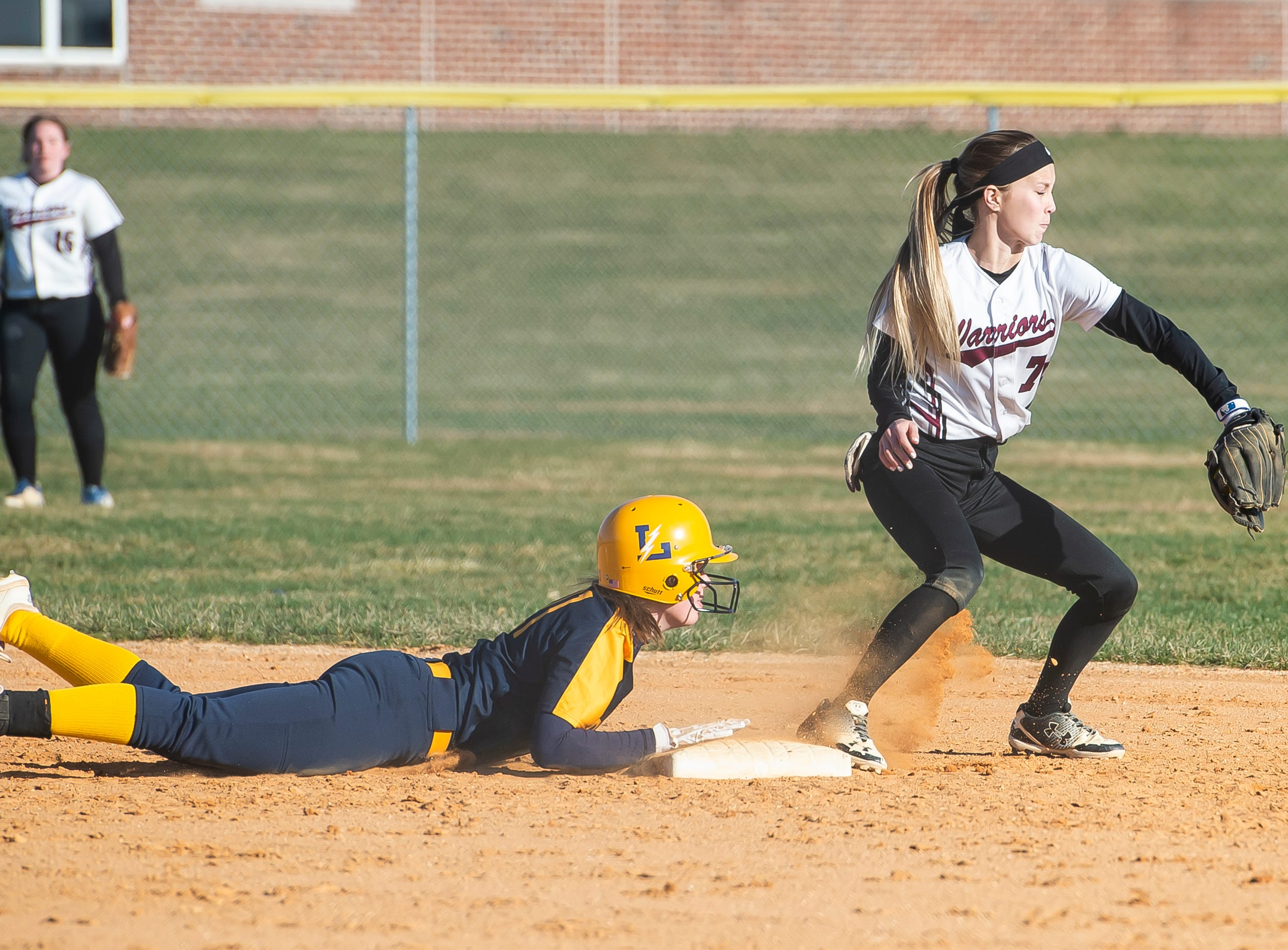Littlestown's Kacie Frock dives head first safely back to the bag during a YAIAA softball game against Gettysburg on Monday, April 1, 2019. The Bolts won 10-4.