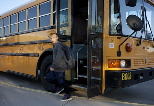 """Zach Norman gets off bus at Desert Harbor Elementary School. New school buses are part of a 0 million bond proposal.  Mark Henle/The Republic 0301121053kh   PNI0307-gl school facilities  03/02/2012   Zach Norman (CQ, 2nd grade) gets off the bus at Desert Harbor Elementary School, 15585 N 91st Avenue, Peoria.  The Peoria Unified School District, like many other districts throughout Arizona, is struggling to keep up with basic building maintenance and equipment repairs. The issue has been exacerbated in recent years due to declining property values and a complete elimination of state """"building renewal"""" funds from the School Facilities Board.  In November, Peoria may ask voters to approve a bond issue in which money to update its aging school bus fleet will be a top priority.  Mark Henle/The Arizona Republic"""