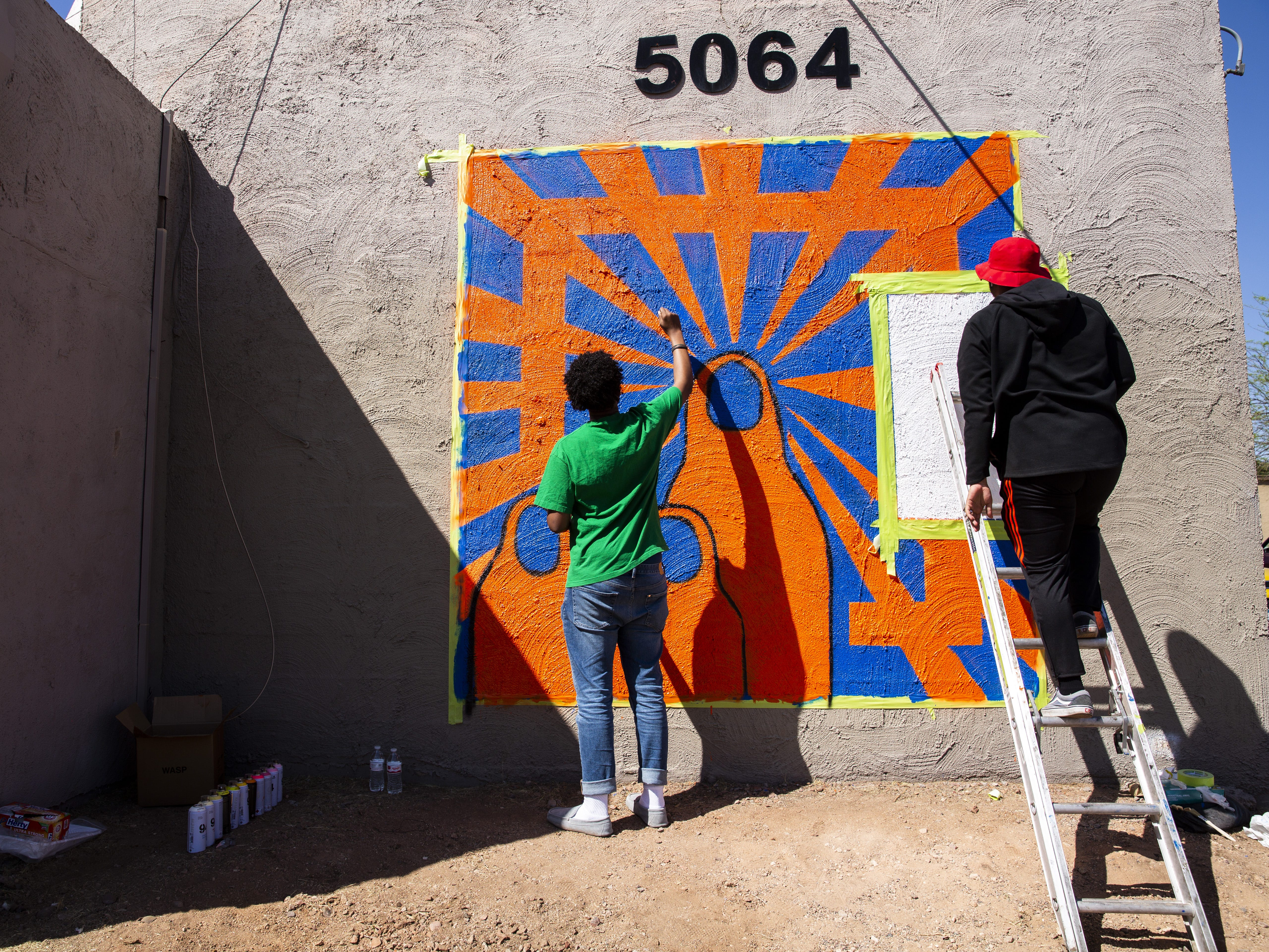 From left, San Diego artists Yaqub Hussein and Haadi Mohamed work on a mural in Phoenix, Ariz. on March 31, 2019.