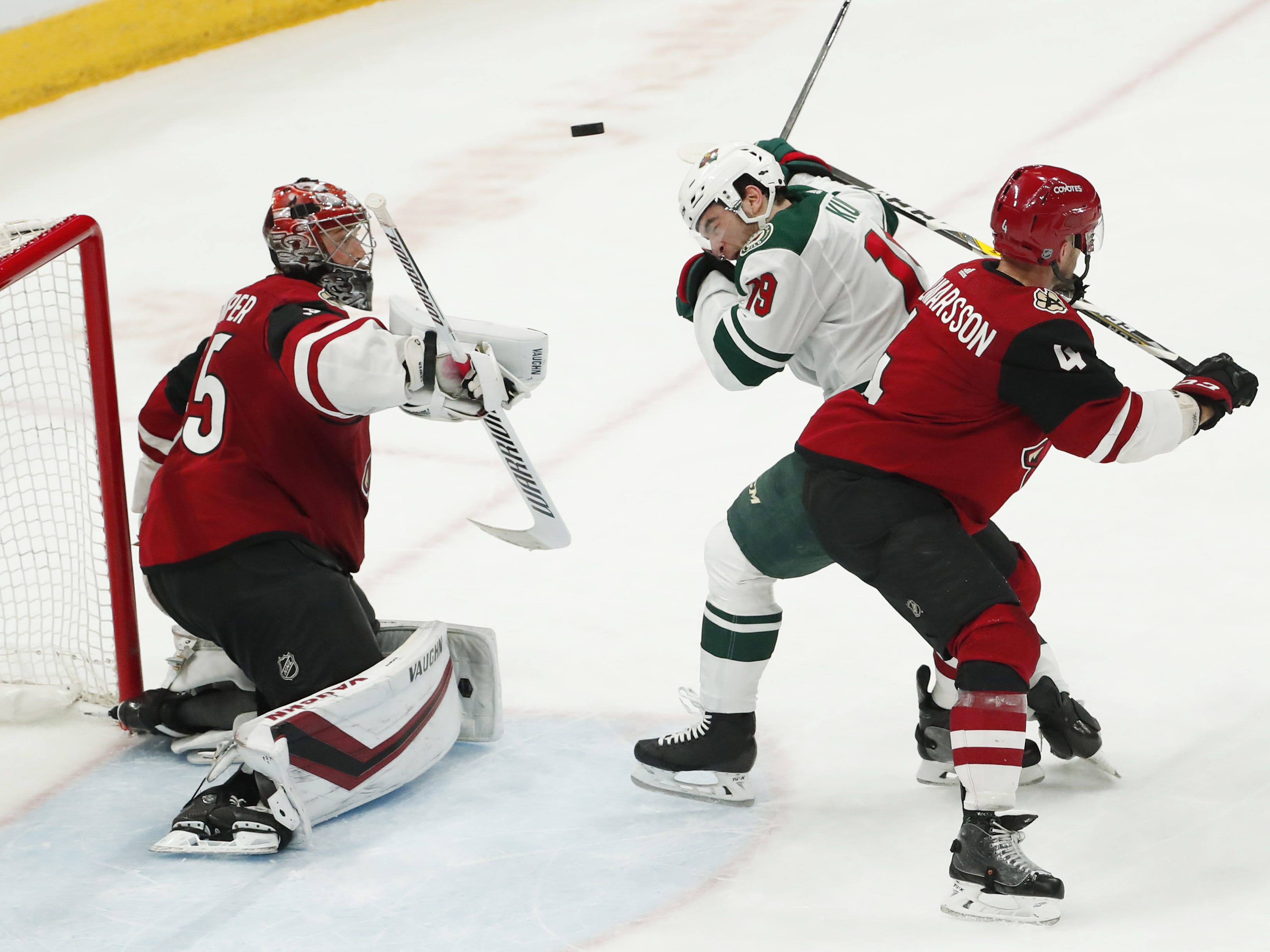 Arizona Coyotes goaltender Darcy Kuemper (35) makes a save as Minnesota Wild center Luke Kunin (19) ducks away from a shot while defended by defenseman Niklas Hjalmarsson (4) during the third period in Glendale March 31, 2019.