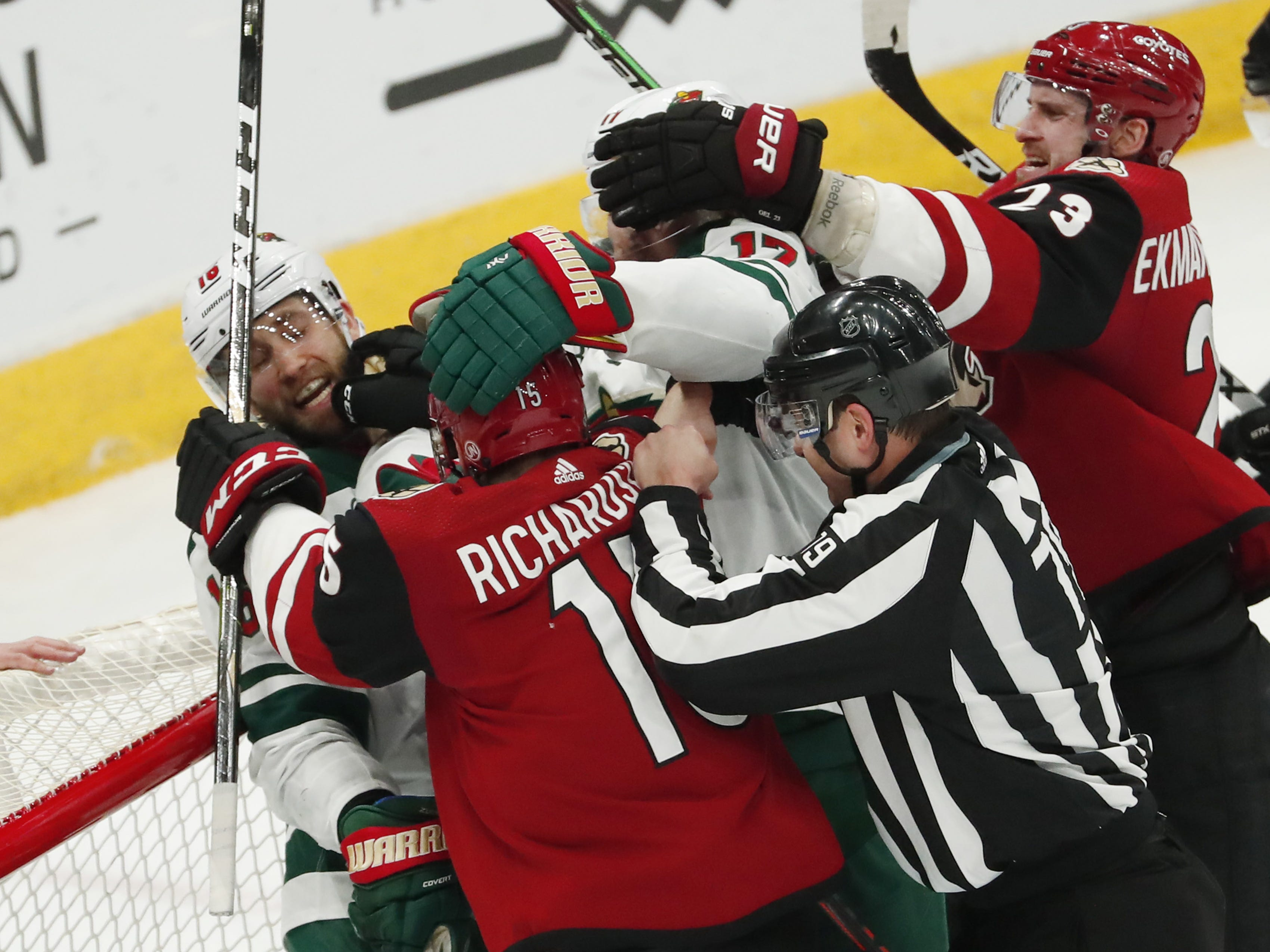 Arizona Coyotes center Brad Richardson (15) mixes it up with Minnesota Wild left wing Jason Zucker (left) during the third period in Glendale March 31, 2019.