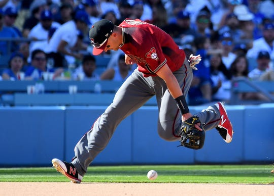 Diamondbacks shortstop Nick Ahmed (13) mishandles an infield hit by Dodgers third baseman Justin Turner (10) allowing him to reach first base in the eighth inning of Sunday's game.