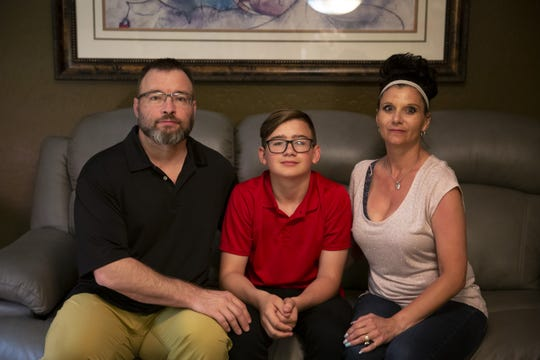 The Schultz family sits on a couch in their Surprise home on March 30, 2019.