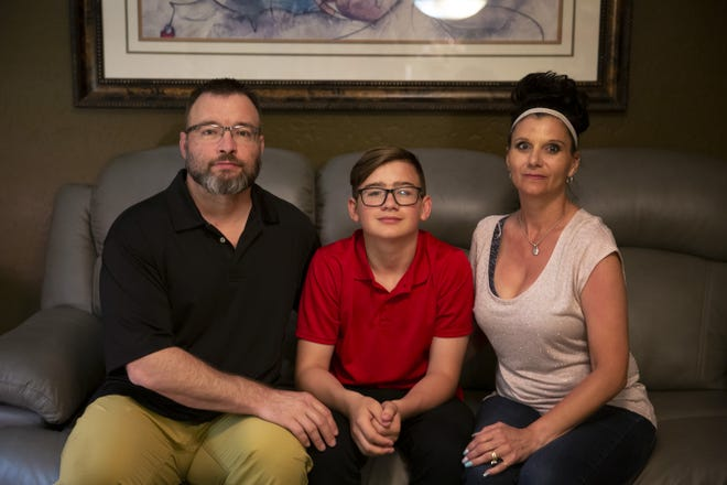 The Schultz family sits on a couch in their Surprise, Arizona, home on March 30, 2019. Eric Schultz's 13-year-old son was suspended after he was caught using a vape pen.