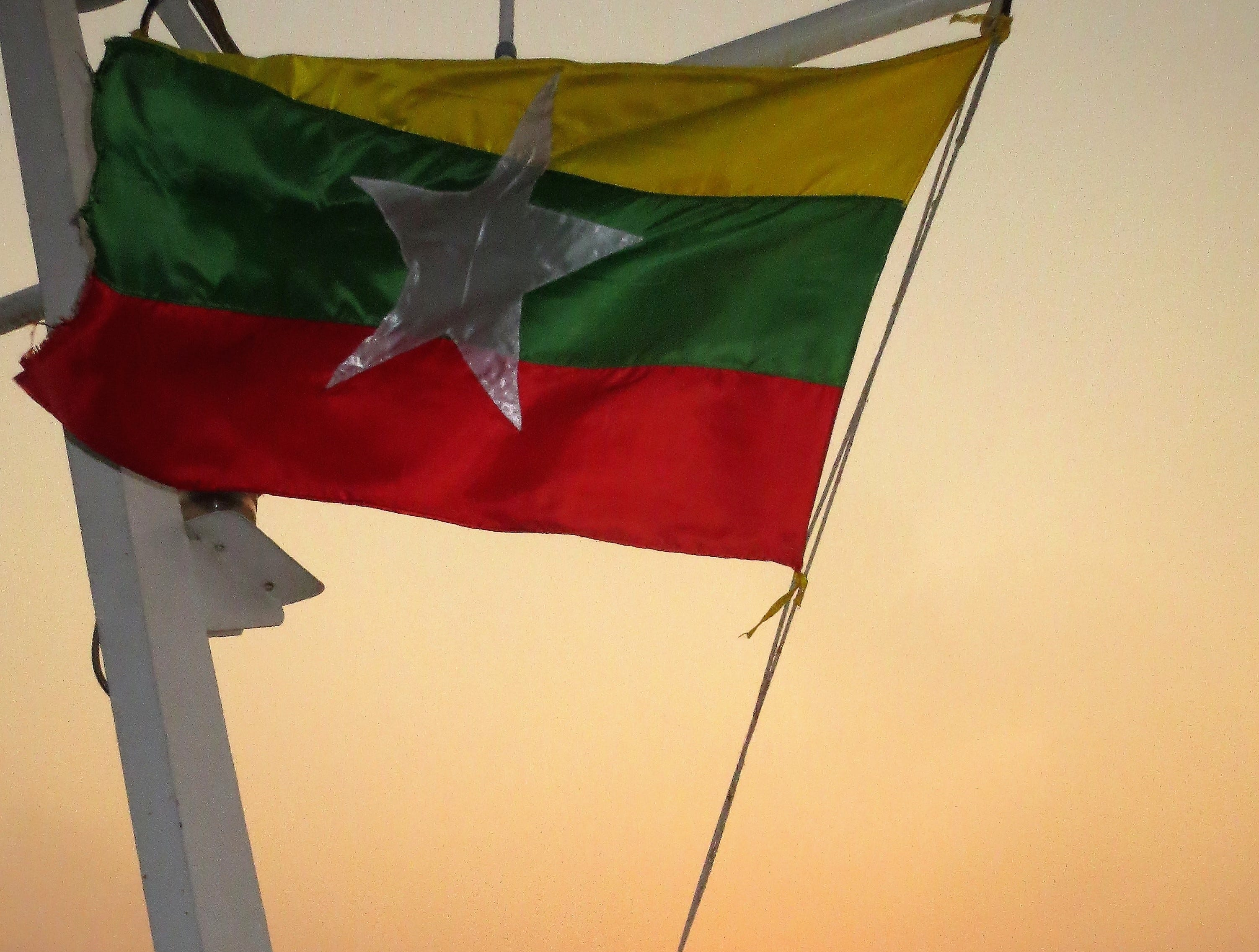 The flag of Myanmar flies on the Scenic Aura river cruiser while the sun sets on the Irrawaddy River.
