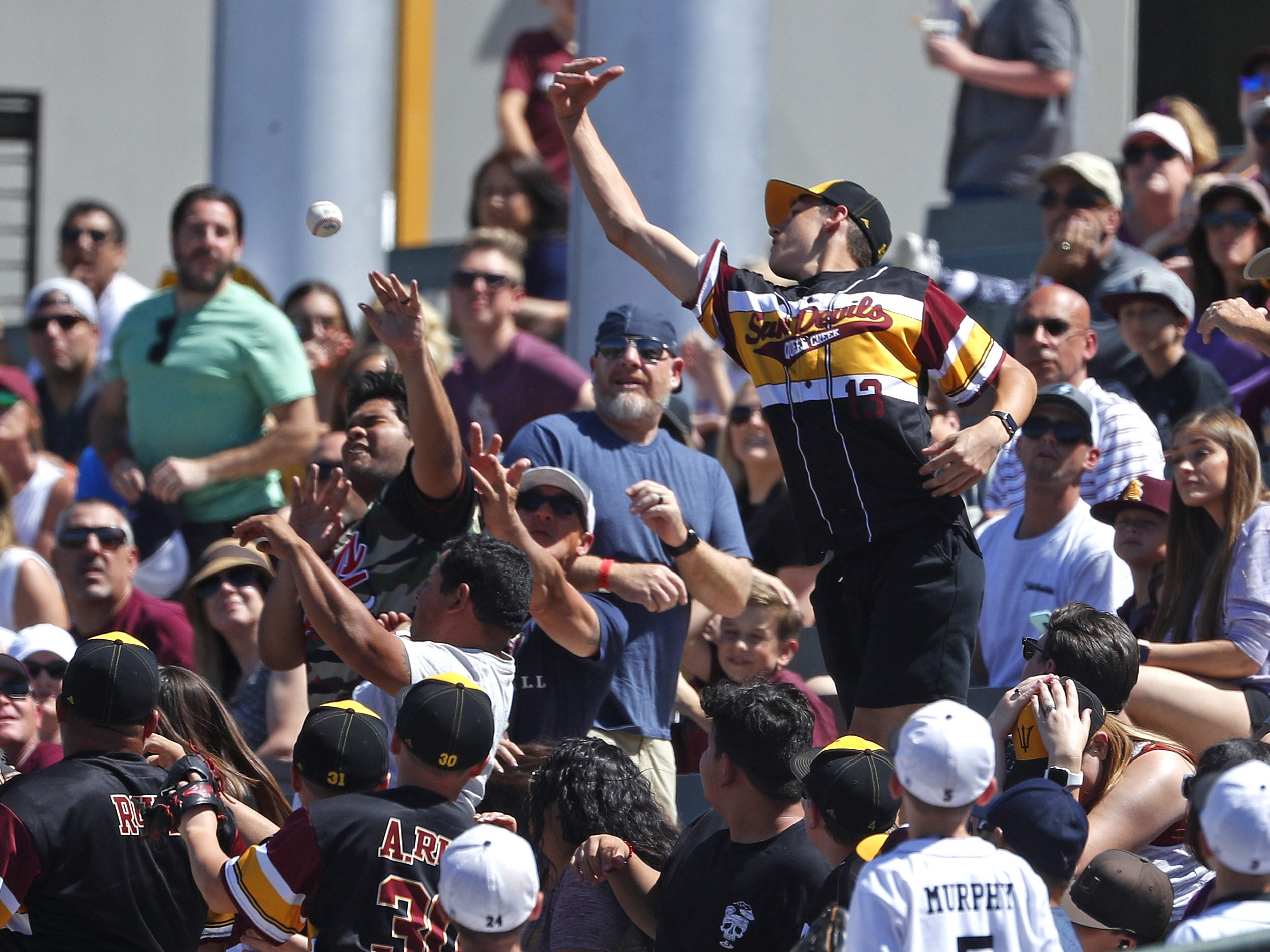 ASU fans try to grab a foul ball during a game against Arizona at Phoenix Municipal Stadium in Phoenix, Ariz. on March 30, 2019.