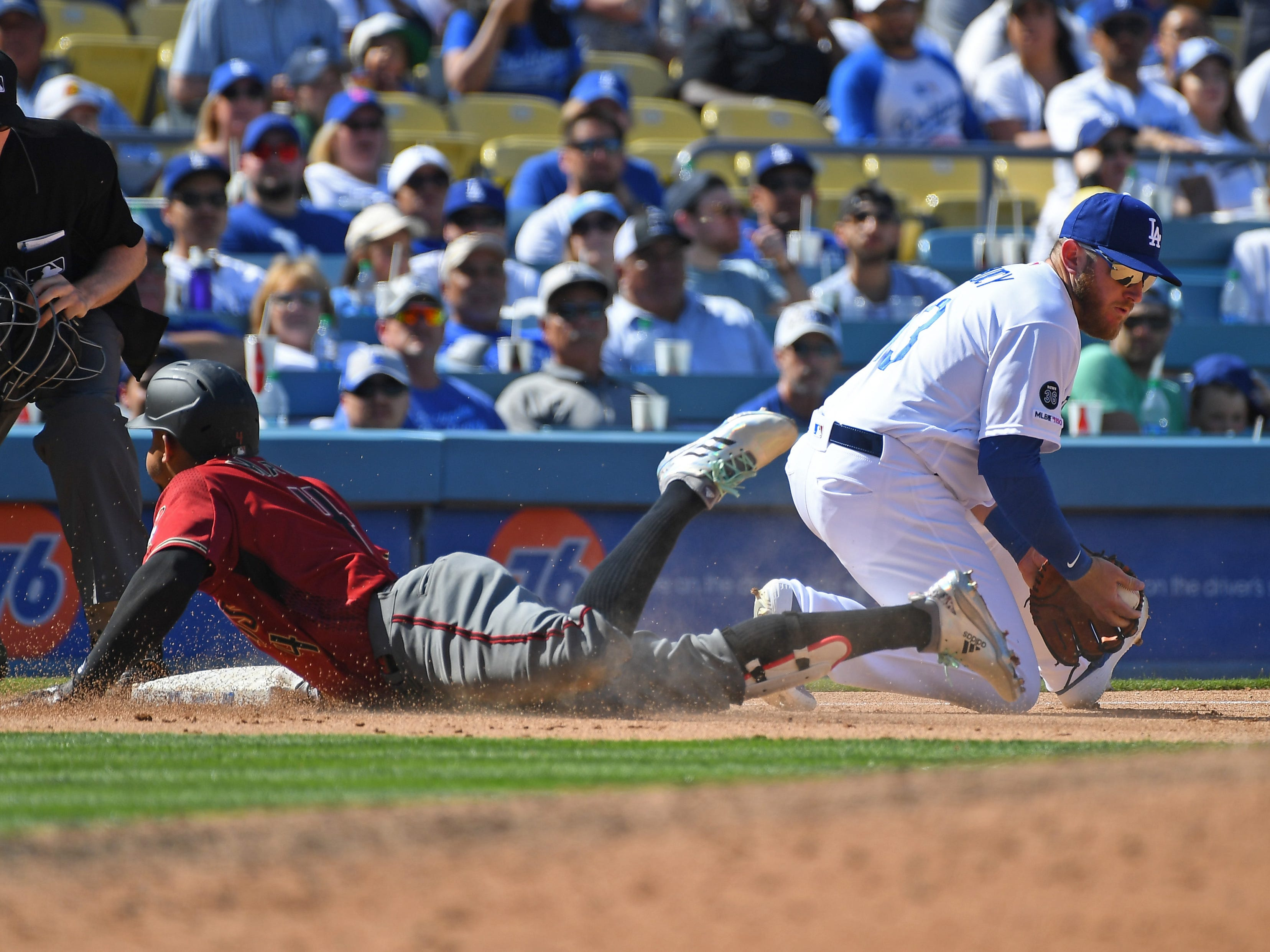 Mar 31, 2019; Los Angeles, CA, USA; Arizona Diamondbacks shortstop Ketel Marte (4) beats the throw to Los Angeles Dodgers third baseman Max Muncy (13) for a triple in the eighth inning of the game at Dodger Stadium.