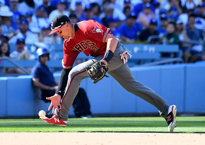 Mar 31, 2019; Los Angeles, CA, USA; Arizona Diamondbacks shortstop Nick Ahmed (13) mishandles an infield hit by Los Angeles Dodgers third baseman Justin Turner (10) allowing him to reach first base in the eighth inning of the game at Dodger Stadium.