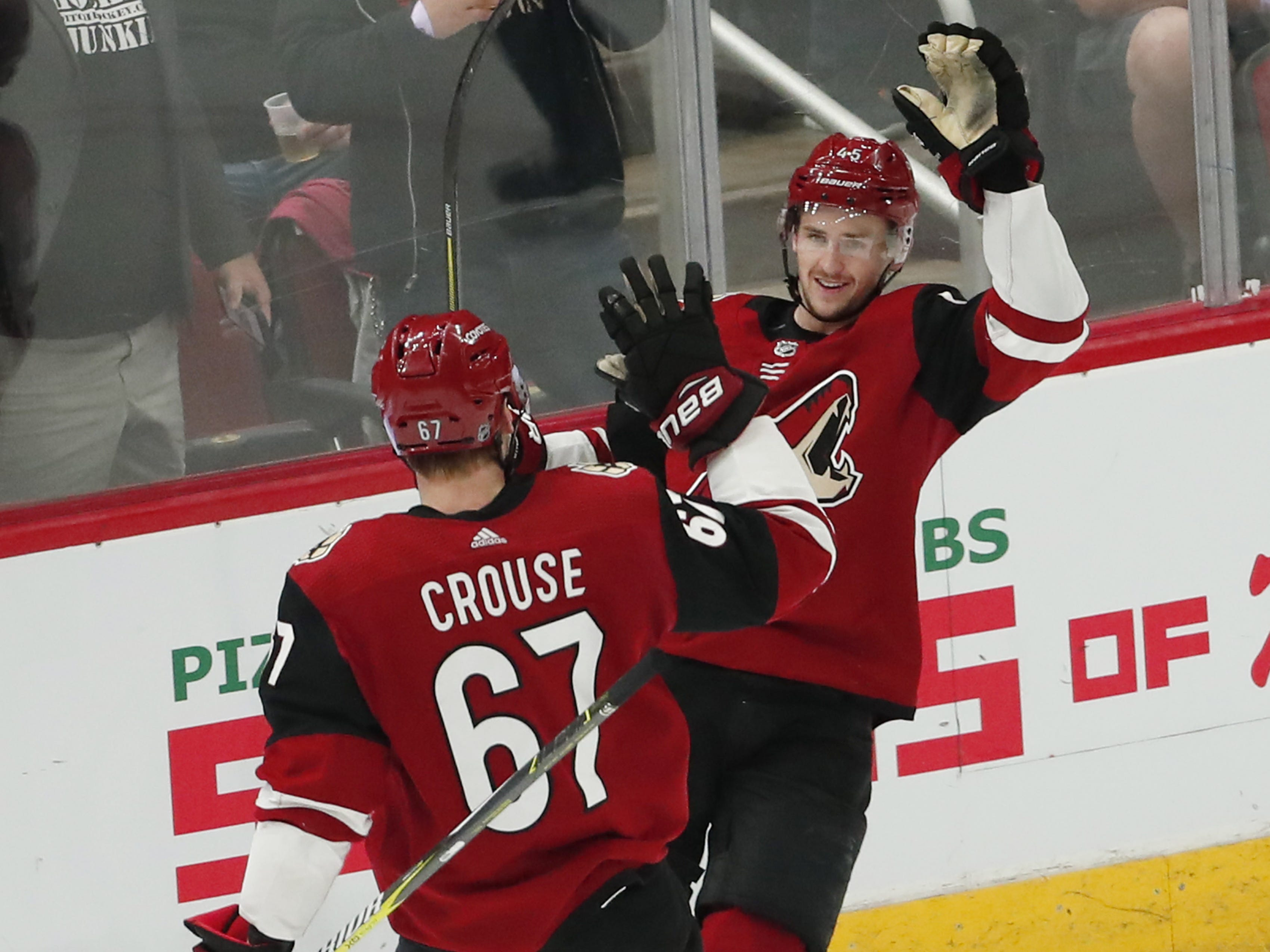Arizona Coyotes right wing Josh Archibald (45) is congratulated by Arizona Coyotes left wing Lawson Crouse (67) after scoring an empty-net goal against the Minnesota Wild during the third period in Glendale March 31, 2019.