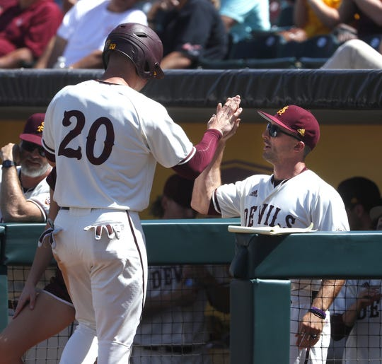 ASU's Spencer Torkelson (20) high-fives hitting coach Michael Earley after Torkelson scored against Arizona during a game at Phoenix Municipal Stadium in Phoenix, Ariz. on March 30, 2019.