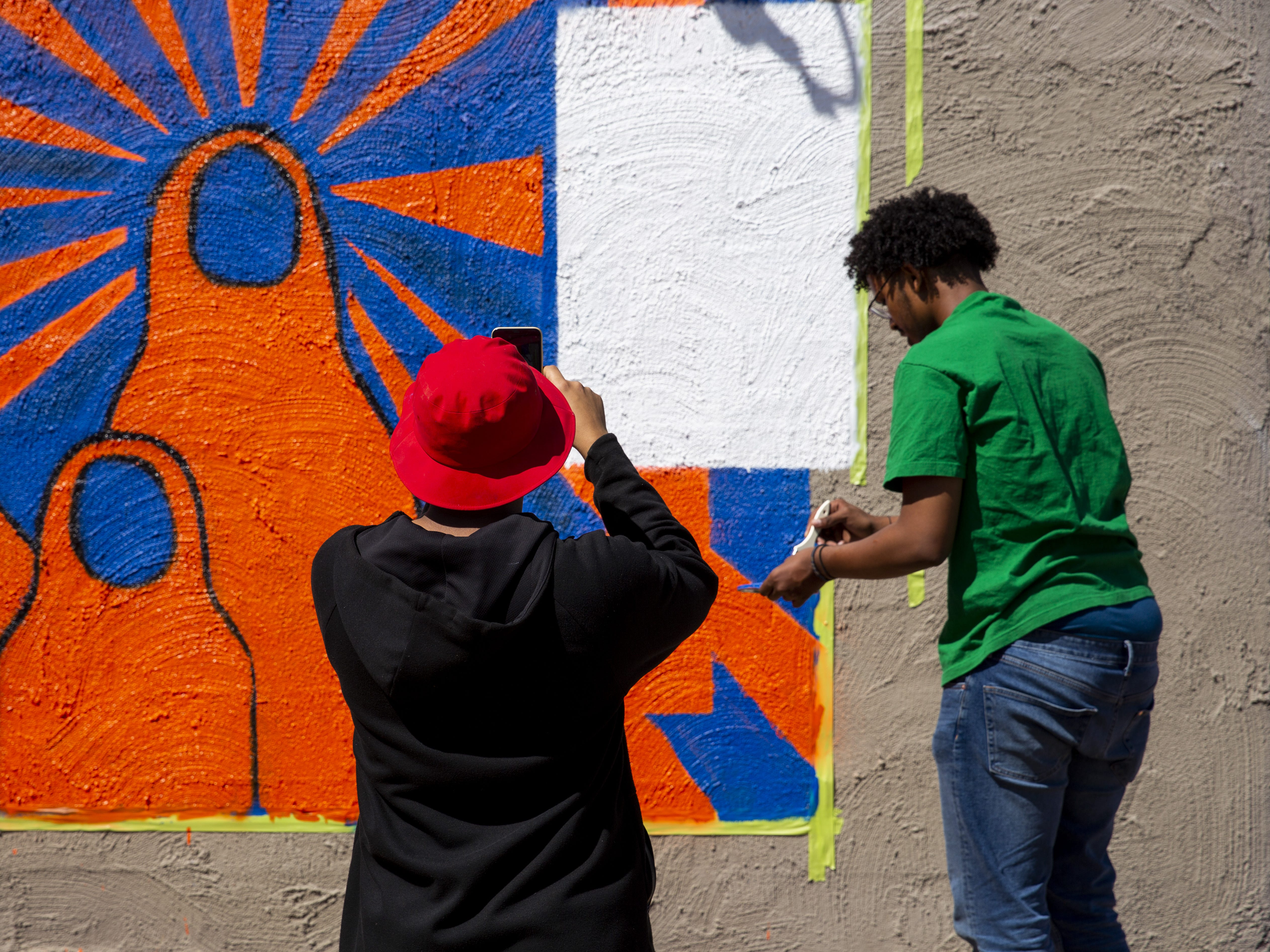 From left, San Diego artists Haadi Mohamed and Yaqub Hussein work on a mural in Phoenix, Ariz. on March 31, 2019.