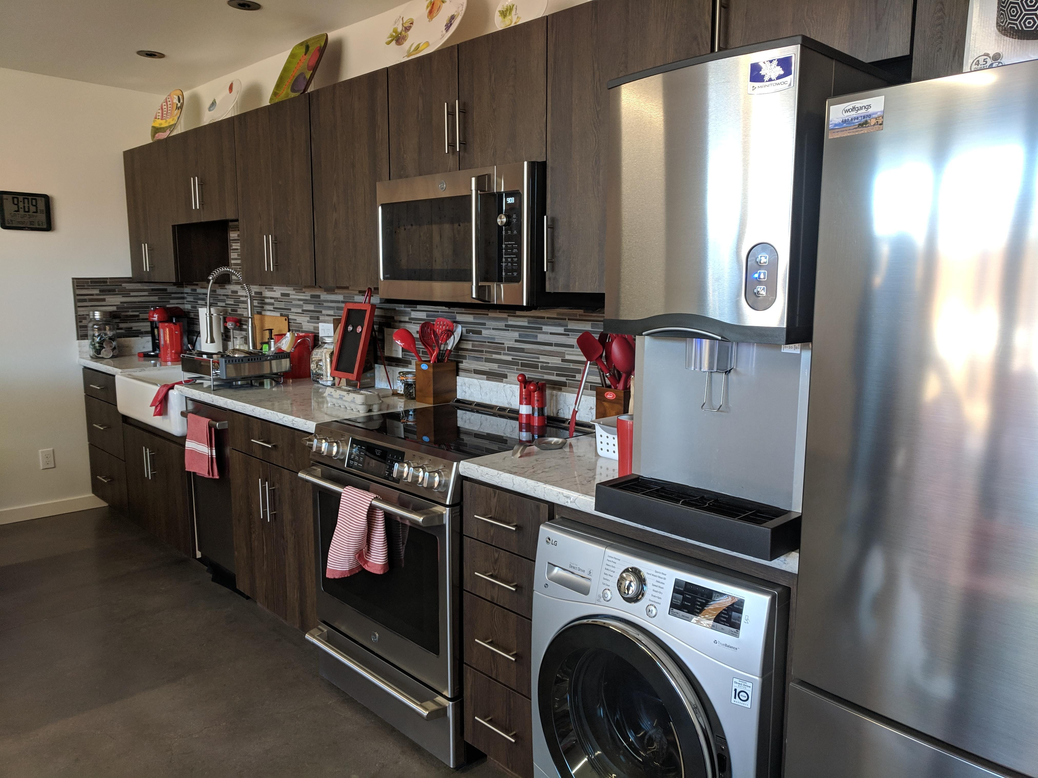 The kitchen features every luxury of any home, including a farmhouse sink and stainless appliances. But, it also doubles as a laundry room, thanks to a single unit that washes and dries dirty farm clothes.