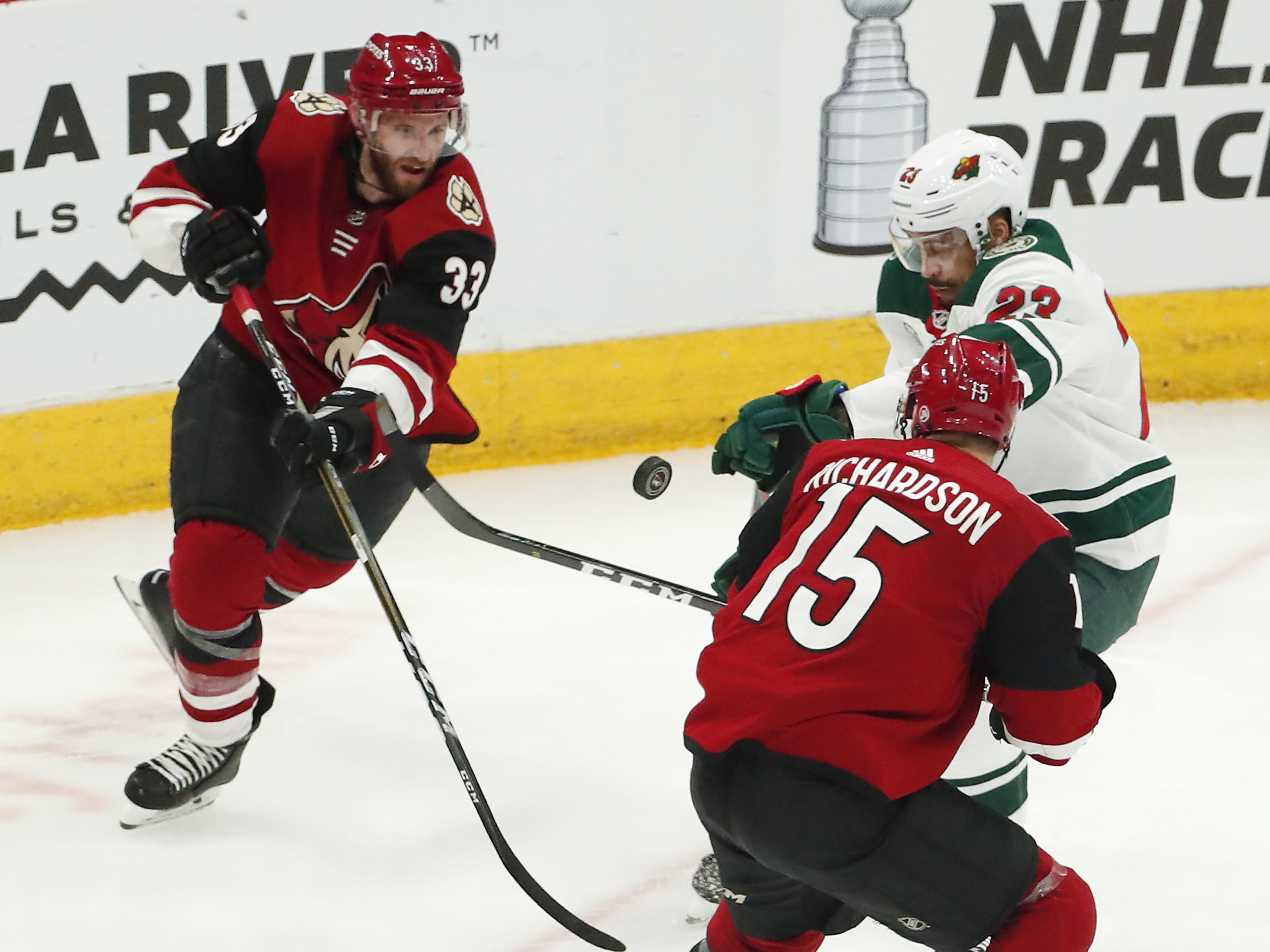 Arizona Coyotes defenseman Alex Goligoski (33) and center Brad Richardson (15) defends Minnesota Wild right wing J.T. Brown (23) during the third period in Glendale March 31, 2019.