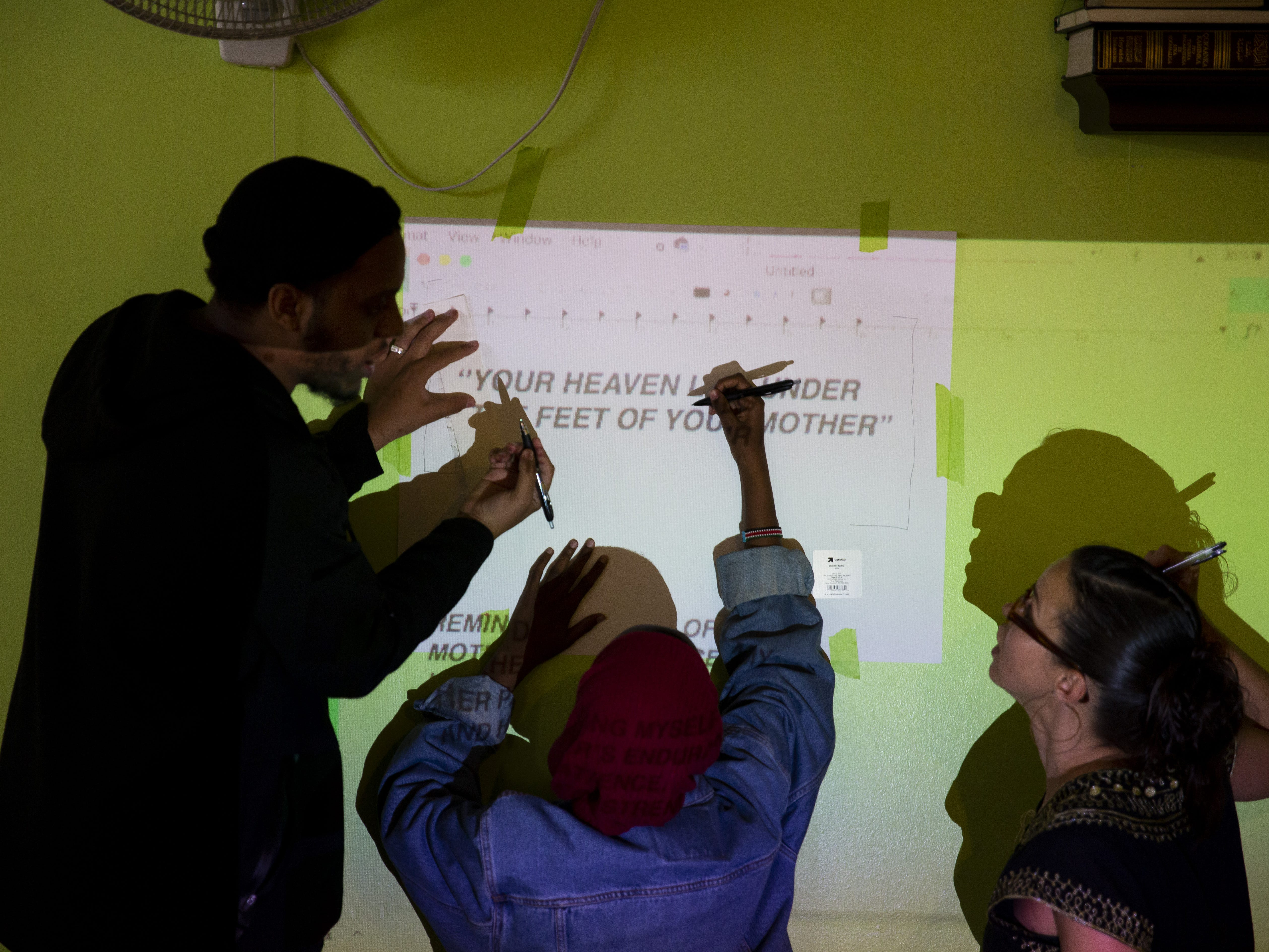 From left, Haadi Mohamed, Faisa Ahmed and Barni Qaasim trace letters of a quote that will be included on the mural in Phoenix, Ariz. on March 31, 2019. Mohamed is an artist from San Diego, Ahmed is an Arizona State University student studying criminology and Qaasim is a member of the Somali Association of Arizona.
