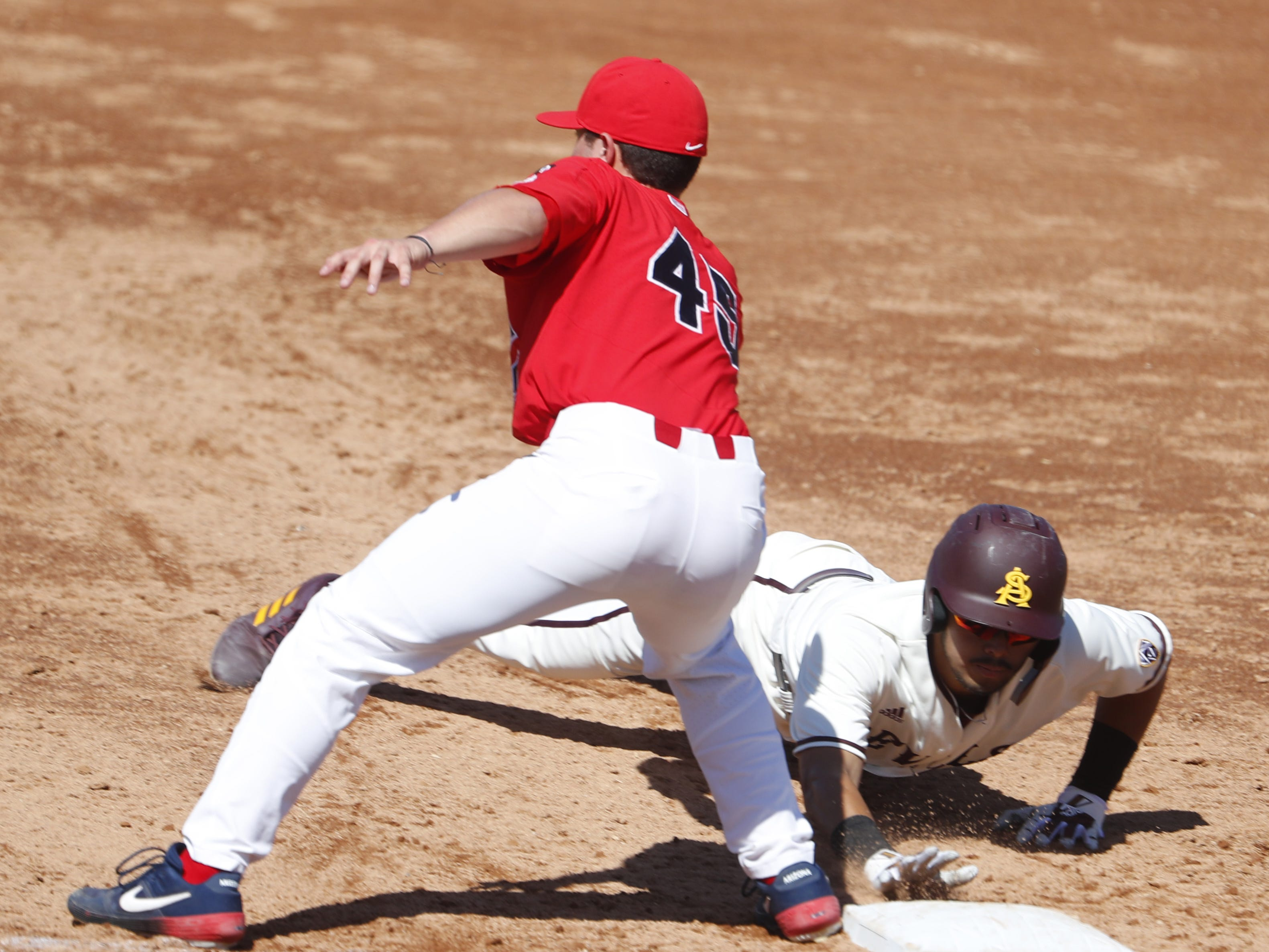 ASU's Lyle Lin (27) slides safely back to first before a tag from Arizona's Branden Boissiere (45) during a game at Phoenix Municipal Stadium in Phoenix, Ariz. on March 30, 2019.