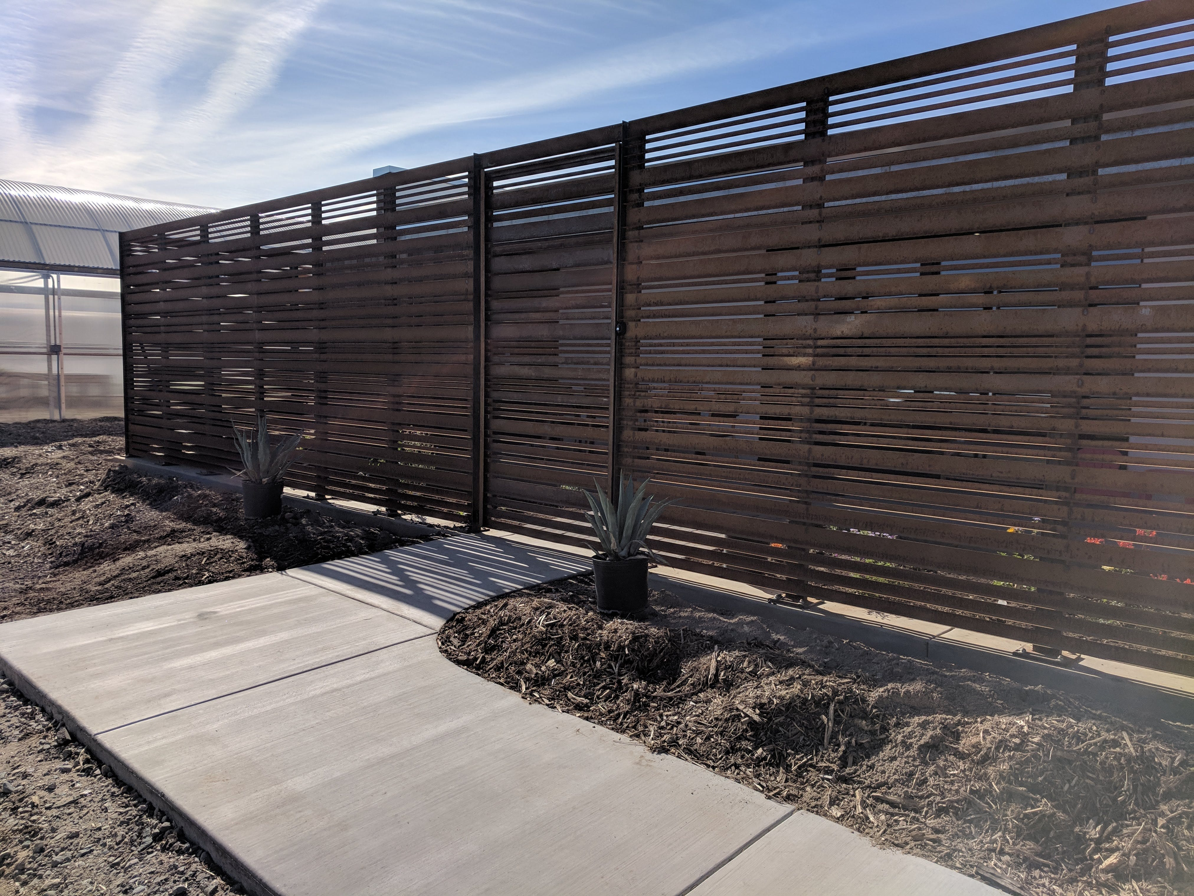 A slatted-steel fence encases the home's front patio, which isn't far from the farm's greenhouse.