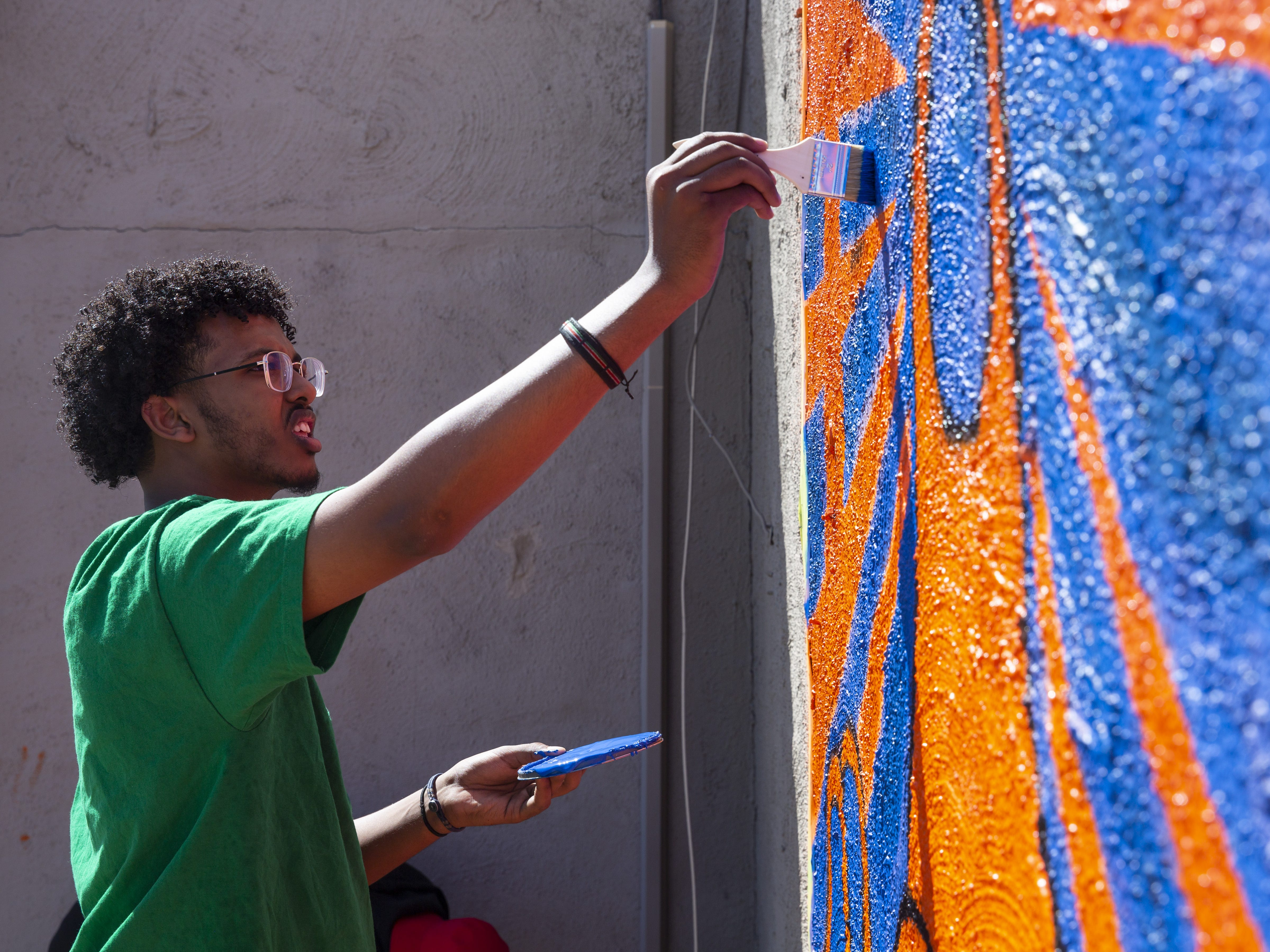 Yaqub Hussein touches up a mural in Phoenix, Ariz. on March 31, 2019.