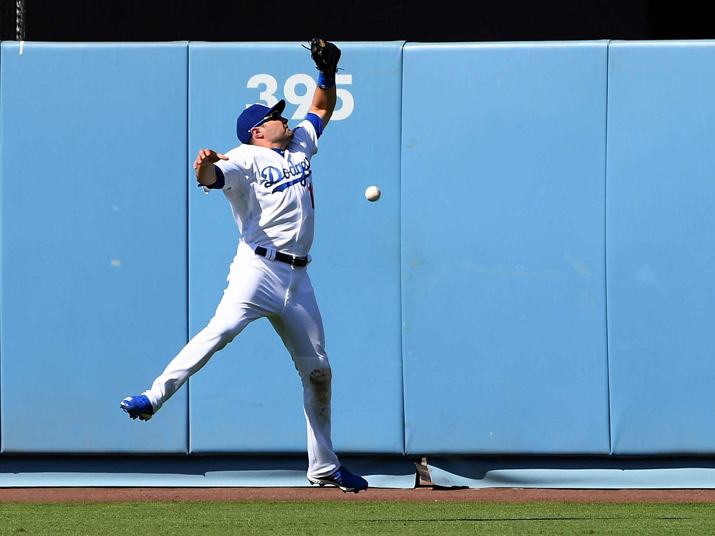 Mar 31, 2019; Los Angeles, CA, USA; Los Angeles Dodgers center fielder A.J. Pollock (11) leaps for a triple hit over his head by Arizona Diamondbacks shortstop Ketel Marte (4) in the eighth inning of the game at Dodger Stadium.