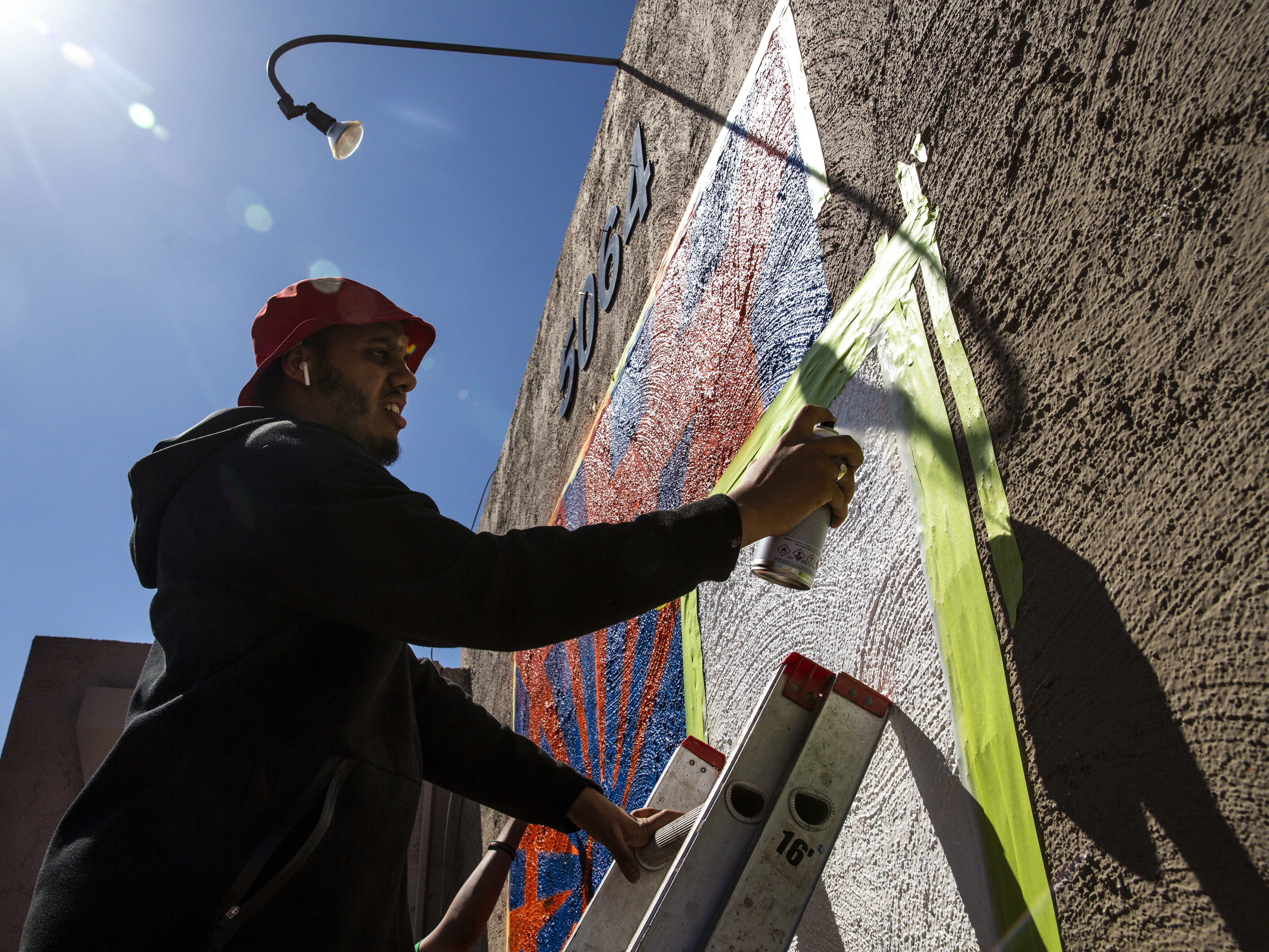 Haadi Hussein sprays white paint on a mural in Phoenix, Ariz. on March 31, 2019.