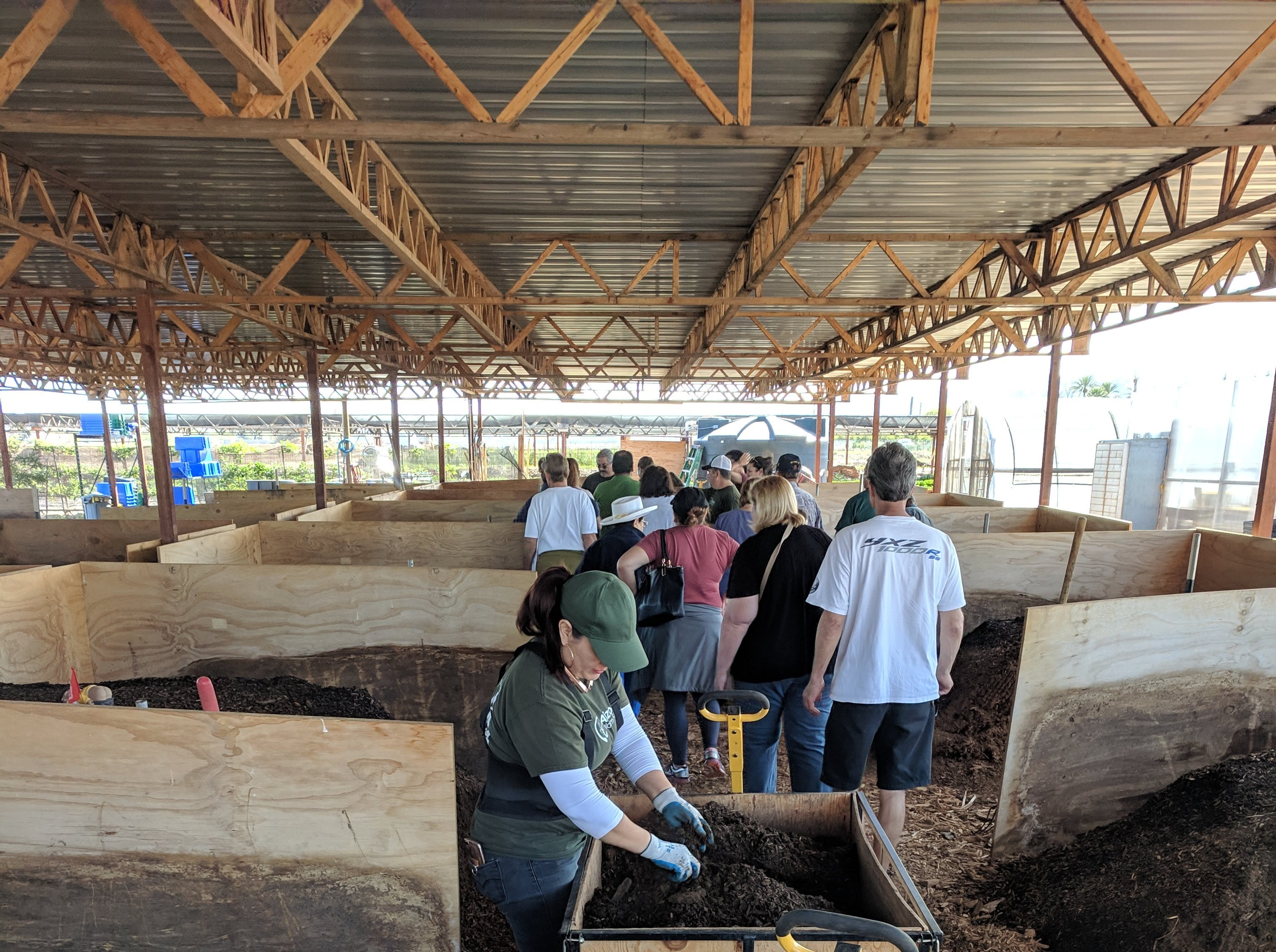 A class tours the farm's compost structure, which is divided into several sections.
