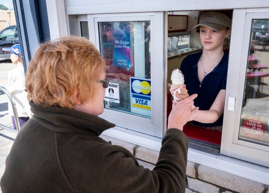 Madelyn Casey, 17, hands a twist-flavored frozen custard cone to Joan Fredendall at free cone day Monday, April 1, 2019 at Jimmy's Frozen Custard in Port Huron.