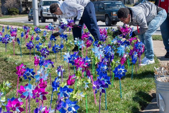 Tysean Beatty, left, and Jamir Williams, both 15, help place pinwheels to raise awareness for reporting child abuse. The teens from the Youth Development Center, a temporary shelter for at-risk kids, were helping to place pinwheels on Monday. The York County Children's Advocacy Center placed hundreds of pinwheels at the intersection of Rathton Road and South George Street in York  in honor of the 800 youths they served in 2018.