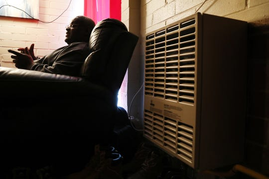 Joseph Harris, a tenant, who helped organize a tenants union, sits in his one bedroom apartment that hasn't had heat since he moved in.  The city has helped with new furnaces for the units that are occupied.