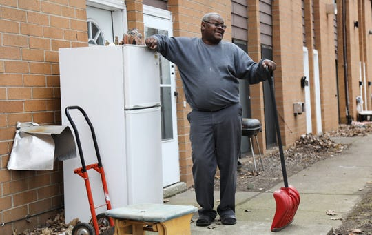 Joseph Harris, a tenant, who helped organize a tenants union, stands outside his apartment with the refrigerator that never worked when he moved in and the shovel he used to clear the walkways at the complex during the winter.