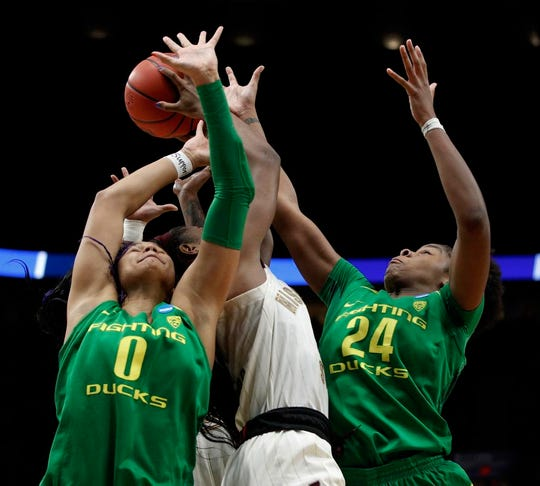 Oregon forwards Satou Sabally, left, and Ruthy Hebard, right, battle for a rebound with Mississippi State forward Anriel Howard, center, during the second half of a regional final in the NCAA women's college basketball tournament Sunday, March 31, 2019, in Portland, Ore. (AP Photo/Steve Dipaola)