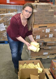 Feeding South Dakota spokeswoman Jennifer Stensaas shows parts of a 40-pound block of cheese from Valley Queen Cheese individually wrapped for distribution on March 28, 2019.