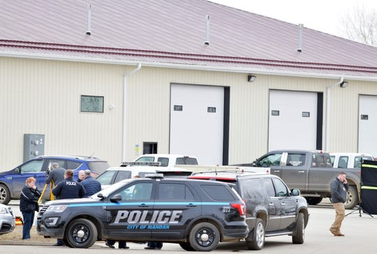 Mandan, N.D. Police Deputy Chief Lori Flaten, left, and other law enforcement personnel stand outside the scene on the south side the RJR Maintenance and Management property in Mandan, N.D., Monday, April 1, 2019.