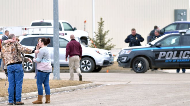 Family and friends console each other at the scene near the south side of the RJR Maintenance and Management building in Mandan, N.D., Monday, April 1, 2019.