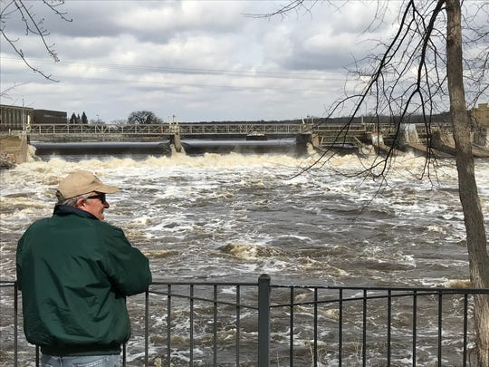 Sartell resident Earl Dullinger watches water roll through the Sartell dam Monday afternoon. Dullinger said he estimates the ice went out above the dam later Saturday afternoon.