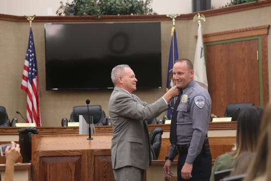 Former Washington City Chief Jim Keith, left, pins stars on new Chief Jason Williams.