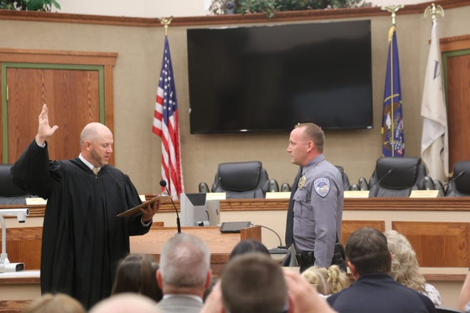 Judge Thad Seegmiller, of the Washington City Justice Court, left, swears in Jason Williams, right, as the new chief of the Washington City Police Department.