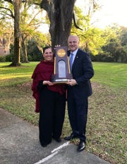 Rep. Mel Ponder poses with FSU coach Lonni Alameda and the 2018 NCAA championship softball trophy