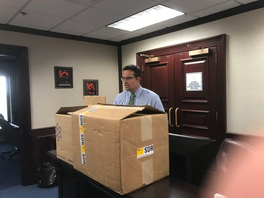 Fred Piccolo, communications director for the Florida House with two boxes of signed petitions asking the House to hear a bill to close the gun show loophole on background checks