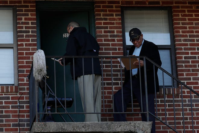 Leon County Schools Superintendent Rocky Hanna and Community Liaison Robert Crawford knock on the door in the Holton Apartment complex to check on a Bond Elementary school student who had missed enough days of school to be considered truant Thursday, Dec. 6, 2018.