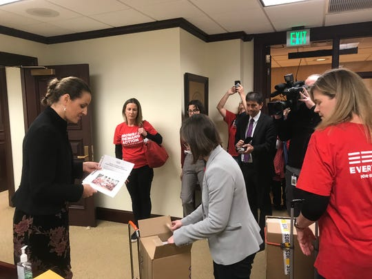Jamie Ito, right in grey, wheeled two boxes with 8,000 petitions into Senate President Bill Galvano's office that request a hearing on a more extensive background check for gun purchases.