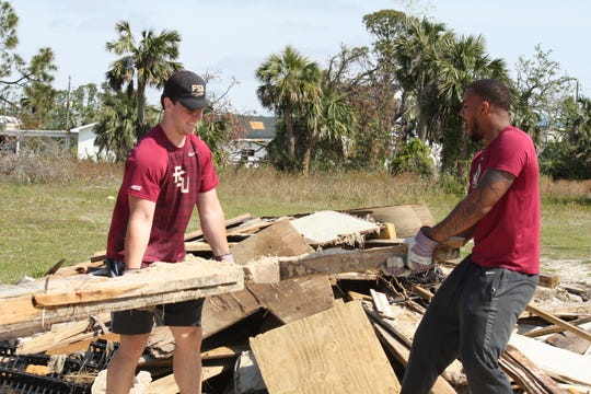 FSU track and field athlete Conor McClain (left) and football player Jaiden Woodbey (right) help clear debris on the beach at the Panama City Marina.