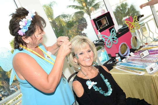 Joanne Soper, left, of Facepaint by Joanne, gives Pam Alverson fairy hair at Ladies' Night Out, a benefit for the Children's Museum of the Treasure Coast.