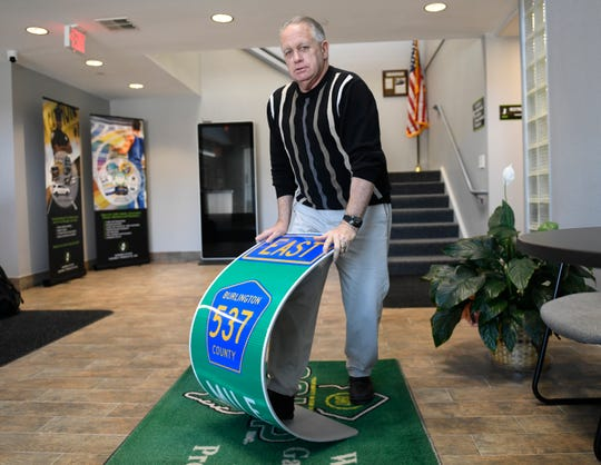 Bob Green, vice president of Garden State Highway Products Inc. in Millville, bends a highway sign made of EcoStrate, a pliable plastic material that is being used as a substitute for aluminum.
