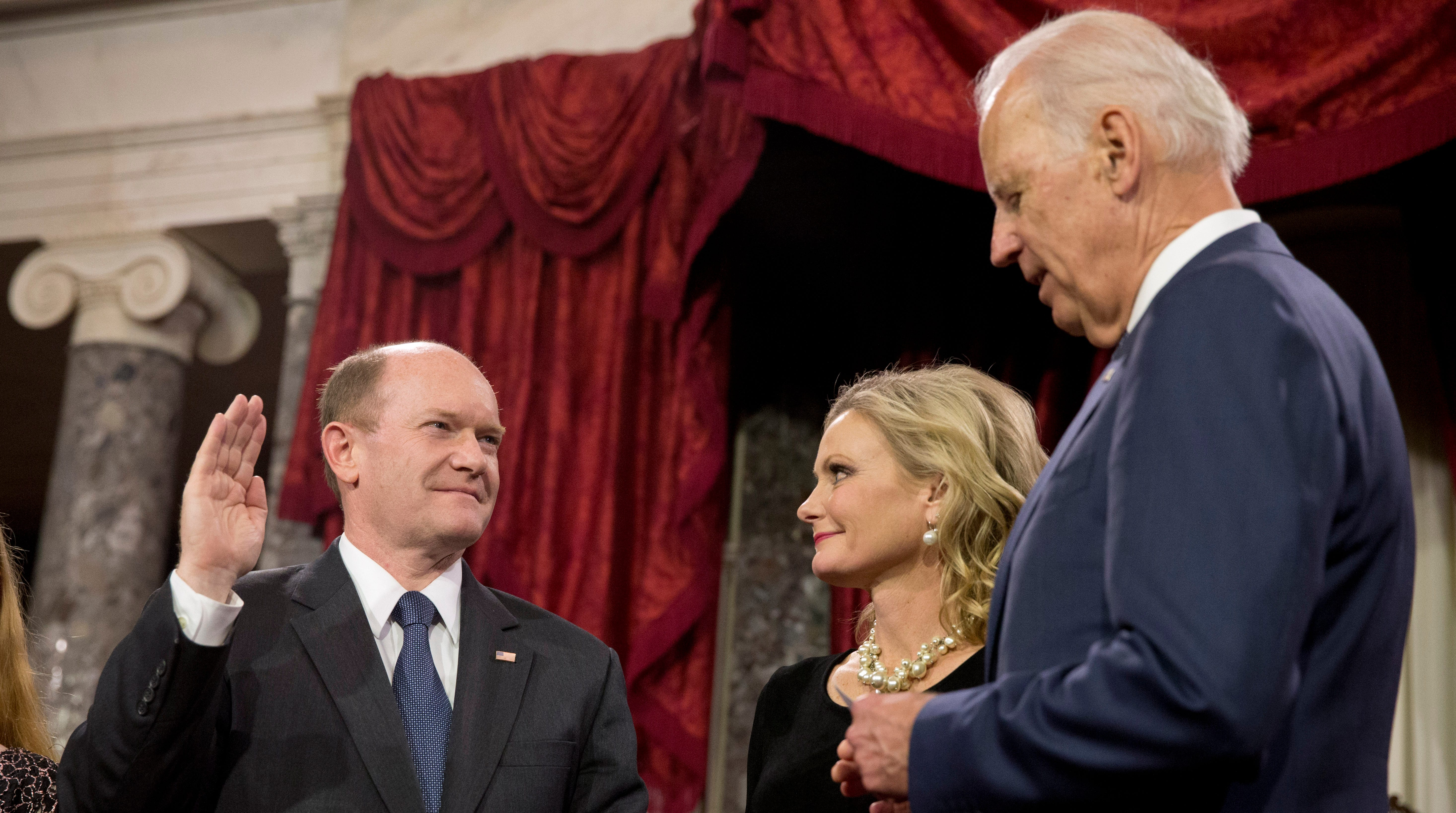 Former Vice President Joe Biden administers the Senate oath to Sen. Chris Coons, D-Del., with wife Annie Coons, during a ceremonial re-enactment swearing-in ceremony, Tuesday, Jan. 6, 2015, in the Old Senate Chamber of Capitol Hill in Washington.