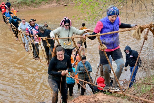 THOR participants crossing the Wichita River, either navigating a rope bridge or wading through the cold, muddy water.