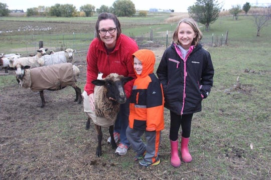 The Benson family of Titonka raise a rare breed of sheep for their wool. Pictured from left are Tara Benson; her son, Tyler, 5; and her daughter, April, 7, with Hope, one of the sheep.