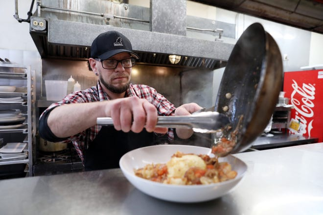 Executive Chef Michael Gorman plates a meal of shrimp and grits at Urban Comforts in downtown Zanesville.
