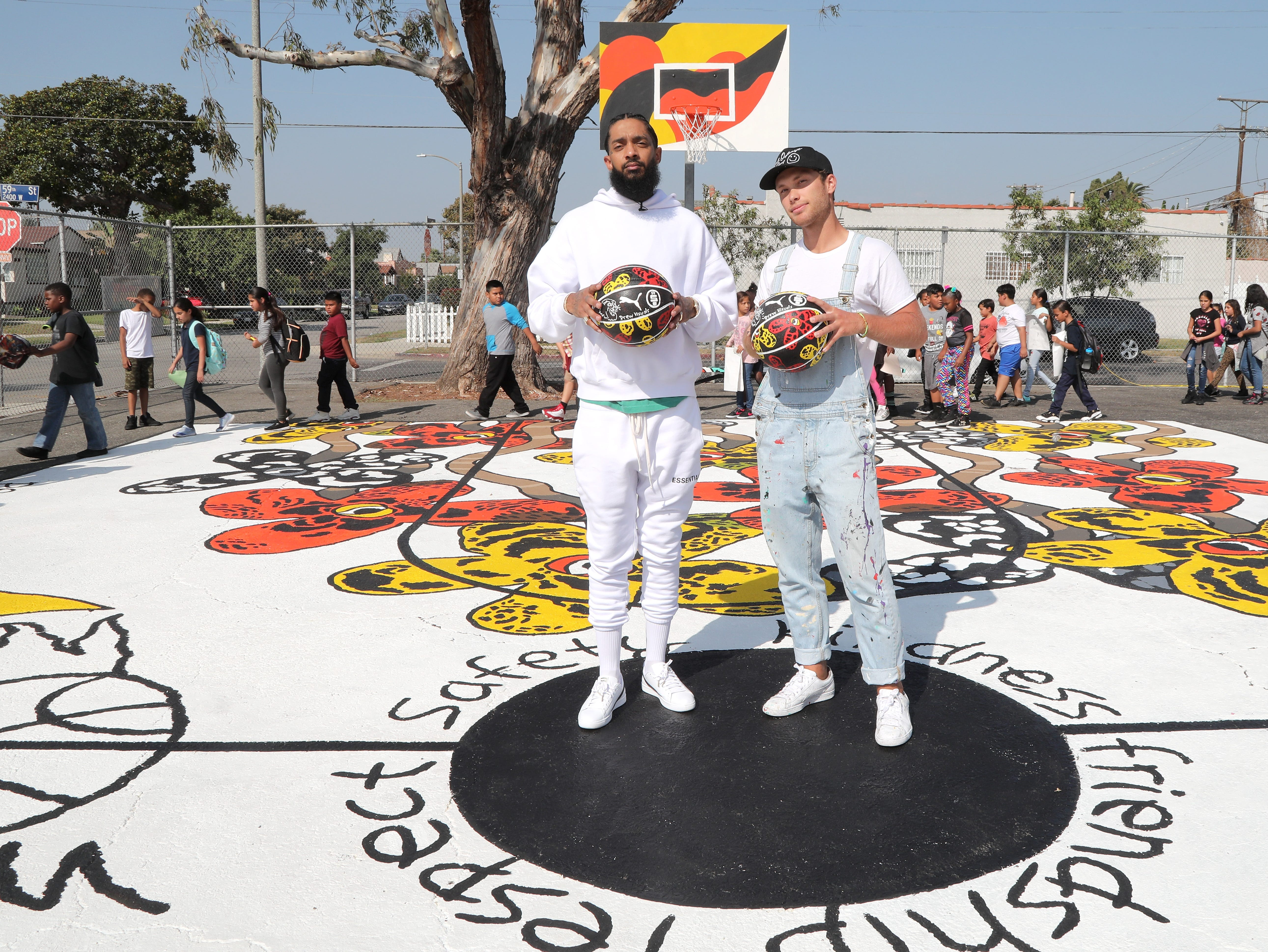 Nipsey Hussle and artist/painter Drew Visuals attend Nipsey Hussle x PUMA Hoops Basketball Court Refurbishment Reveal Event on Oct. 22, 2018, in Los Angeles.