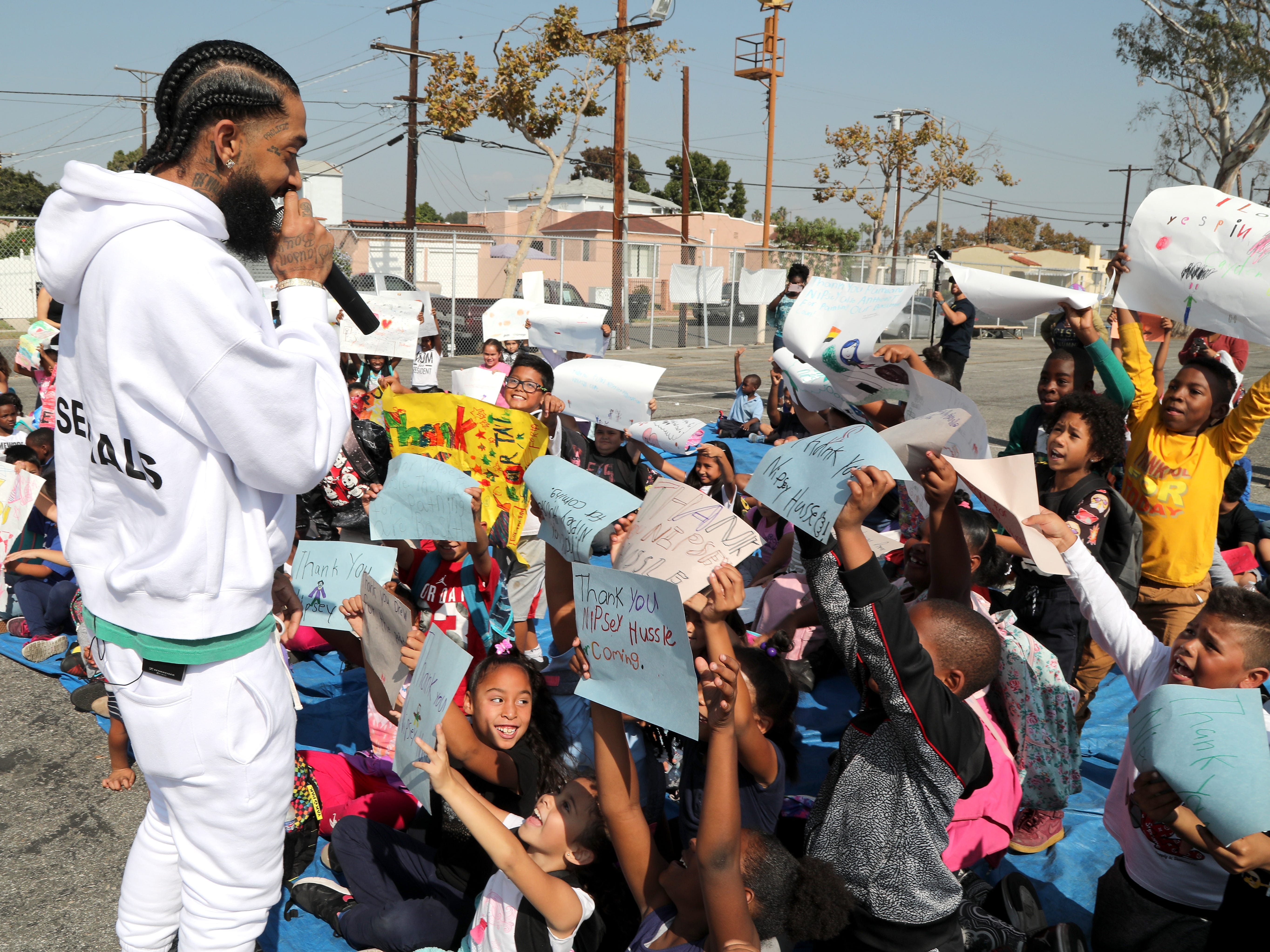 Nipsey Hussle speaks to kids at the Nipsey Hussle x PUMA Hoops Basketball Court Refurbishment Reveal Event on Oct. 22, 2018, in Los Angeles.