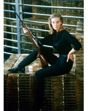 """Tania Mallet sits on a pile of gold bullion in Fort Knox, for her role as Tilly Masterson in """"Goldfinger"""" in 1964."""