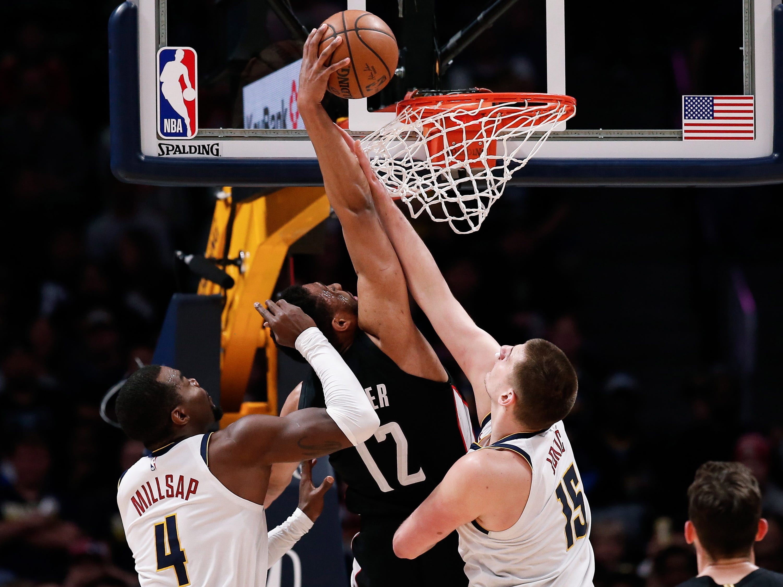 March 31: Wizards forward Jabari Parker (12) throws down the one-handed slam between Nuggets defenders Paul Millsap (4) and Nikola Jokic (15) during the first half in Denver.